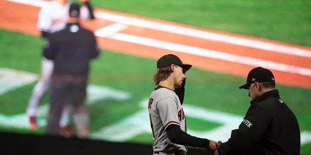 Arizona Diamondbacks starting pitcher Luke Weaver (24) has his equipment checked for foreign substances by first base umpire Dan Iassogna during the fourth inning of a baseball game, Tuesday, Sept. 28, 2021, in San Francisco.