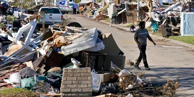 Lyndell Scott walks past the debris of his gutted home in the aftermath of Hurricane Ida in LaPlace, La., Friday, Sept. 10, 2021.