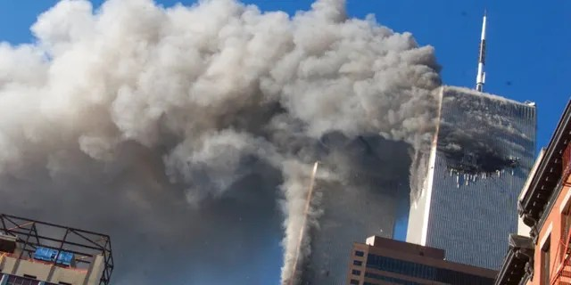 FILE - Smoke rises from the burning twin towers of the World Trade Center after hijacked planes crashed into the towers on September 11, 2001 in New York City. Associated Press photographer Richard Drew talks about AP's coverage of 9/11 and the events that followed.