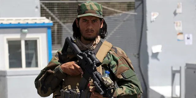 A Taliban soldier stands guard at the gate of Hamid Karzai International Airport in Kabul, Afghanistan, Sunday, Sept. 5, 2021. Some domestic flights have resumed at Kabul's airport, with the state-run Ariana Afghan Airlines operating flights to three provinces. (AP Photo/Wali Sabawoon)