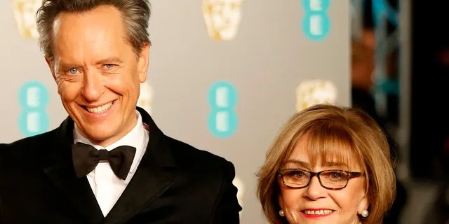 British actor Richard E. Grant (C) poses on the red carpet with his wife Joan Washington (R) upon arrival at the BAFTA British Academy Film Awards at the Royal Albert Hall in London on February 10, 2019.