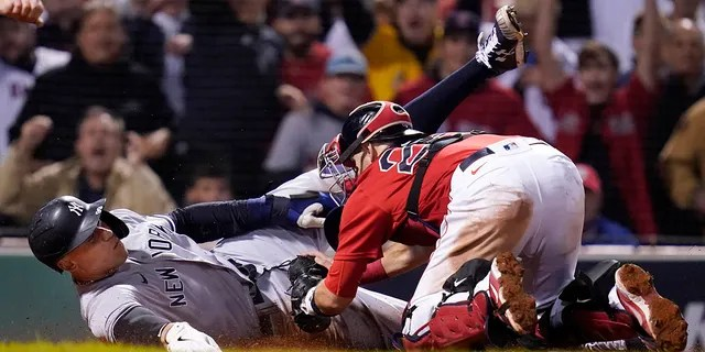 New York Yankees' Aaron Judge is tagged out at the plate by Boston Red Sox catcher Kevin Plawecki as he tries to score on a single by Giancarlo Stanton in the sixth inning of an American League Wild Card playoff baseball game at Fenway Park, Tuesday, Oct. 5, 2021, in Boston.