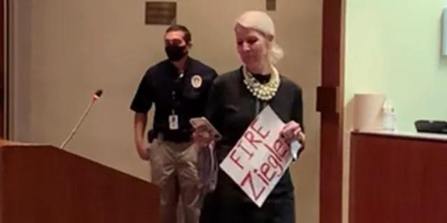 "A Loudoun County, Virginia, mom enters a school board meeting with a sign reading ""Fire Ziegler,"" Oct. 12, 2021."