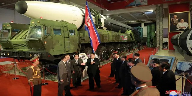In this photo provided by the North Korean government, North Korean leader Kim Jong Un, center, speaks in front of what the North says an intercontinental ballistic missile displayed at an exhibition of weapons systems in Pyongyang, North Korea, on Monday.