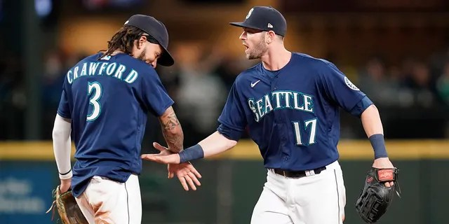 Seattle Mariners' Mitch Haniger (17) and J.P. Crawford (3) share congratulations after the team beat the Los Angeles Angels in a baseball game Saturday, Oct. 2, 2021, in Seattle. The Mariners won 6-4.