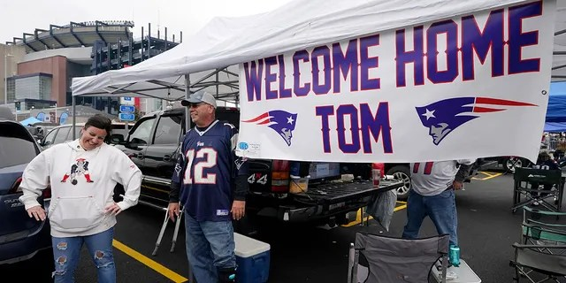 New England Patriots fan Stephanie Lamontagne, left, of Merrimack, N.H., smiles while chatting with Bill Gately, of Burrillville, R.I., while tailgating near a sign greeting the return of quarterback Tom Brady prior to a game between the New England Patriots and Tampa Bay Buccaneers, Sunday, Oct. 3, 2021, in Foxborough, Mass.