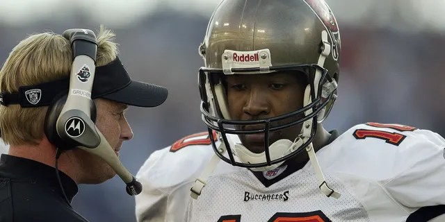 Quarterback Shaun King (10) of the Tampa Bay Buccaneers talks to head coach Jon Gruden during the game against the Tennessee Titans on Dec. 28, 2003, at The Coliseum in Nashville, Tennessee.