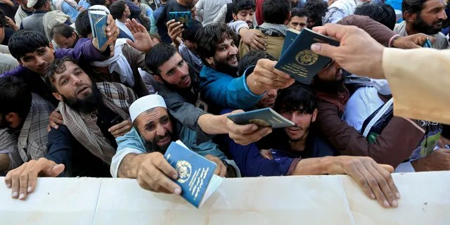 FILE PHOTO: Afghan men wait to collect tokens needed to apply for the Pakistan visa, in Jalalabad, Afghanistan October 21, 2020. REUTERS/Stringer/File Photo