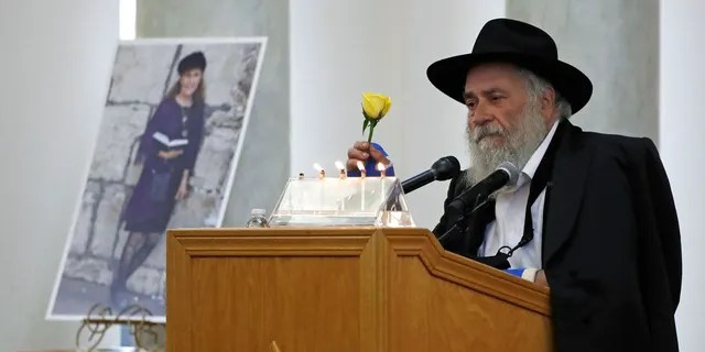 In this April 29, 2019, file photo, Yisroel Goldstein, Rabbi of Chabad of Poway, holds a yellow rose as he speaks at the funeral for Lori Kaye, who is pictured at left, in Poway, Calif. Kaye, who was was killed April 27, 2019, when a gunman opened fire inside the Chabad of Poway synagogue, had given Goldstein the flower as part of a bouquet the day before the shooting, which also injured Goldstein. (AP Photo/Gregory Bull, File)