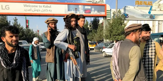 A member of Taliban (C) stands outside Hamid Karzai International Airport in Kabul, Afghanistan, August 16. REUTERS/Stringer