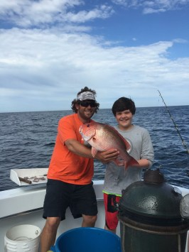 Big smiles from NC angler Root Jr showing off his red snapper caught deep sea fishing Spring 2015 on the Jamie G