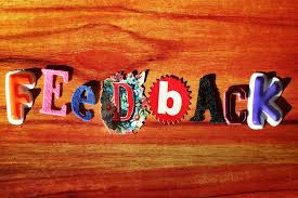 "The word ""feedback"" created in felt letters on a wooden background."