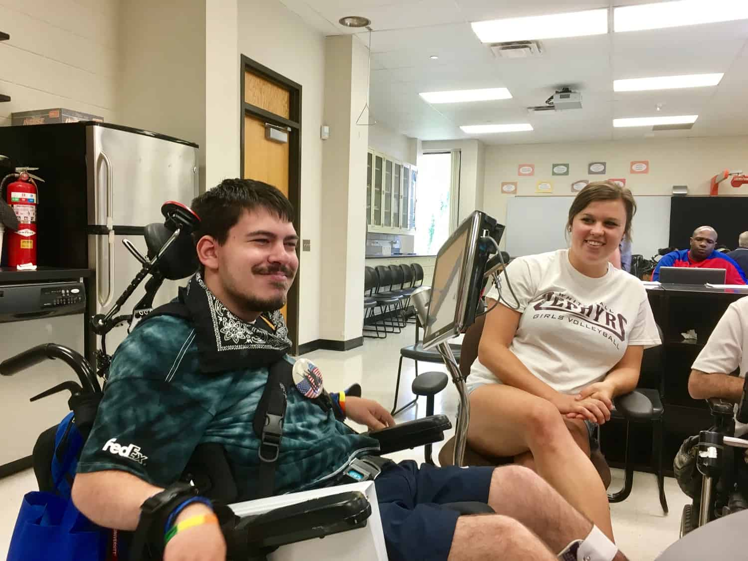 Image of young man with AAC device and his communication partner.