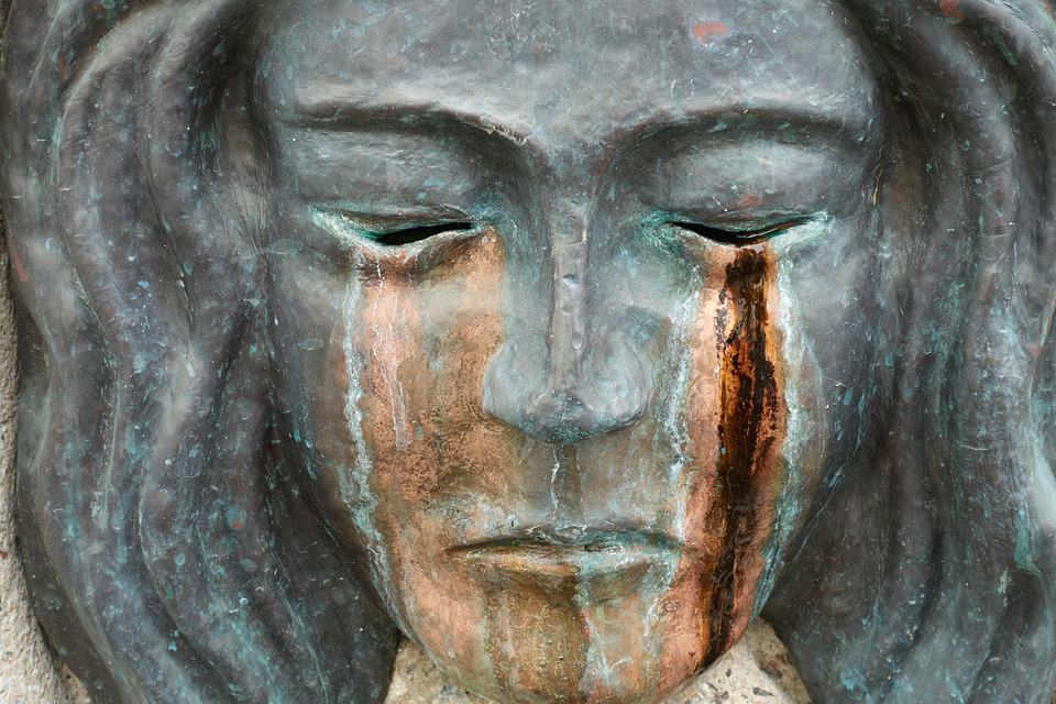 The face of a stone statue with tears.