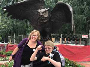 Image of two people, one in a wheelchair, posing in front of Temple Owl statue