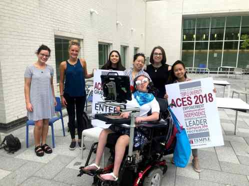 Image of AAC user in wheelchair surrounded by ACES volunteers and rocking awesome sunglasses.