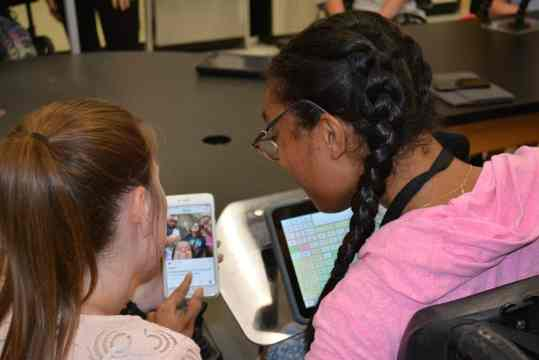 TWo young women, one with an AAC device, looking at a selfie.