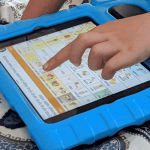 Young child's finger pointing to icon on aac device