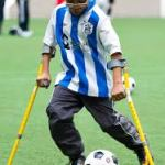 boy playing soccer with crutches