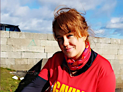 Ruby Cooney, a young Irish woman sitting on the ground in front of a stone wall, smiling. She wears a bright red shirt.