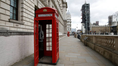 The door of a red London telephone box hangs open on a empty street near the Houses of Parliament in London on April 2, 2020 © AFP / Tolga Akmen