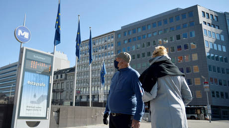 FILE PHOTO. A couple wearing protective face masks walks past the European Commission headquarters in Brussels, Belgium.