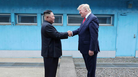 FILE PHOTO: US President Donald Trump shakes hands with North Korean leader Kim Jong Un as they meet at the demilitarized zone.