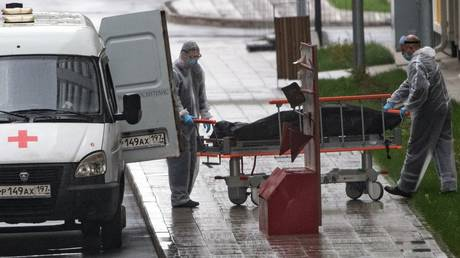 Staff transport a body of a patient from a medical facility for Covid-19 patients in Moscow. © Sputnik