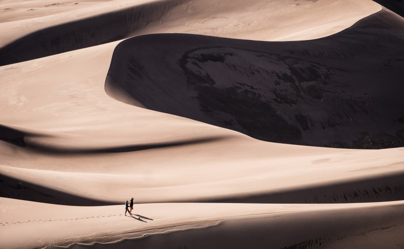 Two people dwarfed by dunes