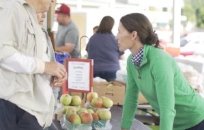 Elizabeth shares Melrose apples with FMO customers.