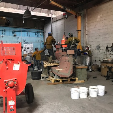 Pouring 550 pounds of molen metal into a large sand mold