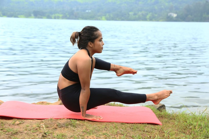 a girl performing the elephant trunk pose in yoga