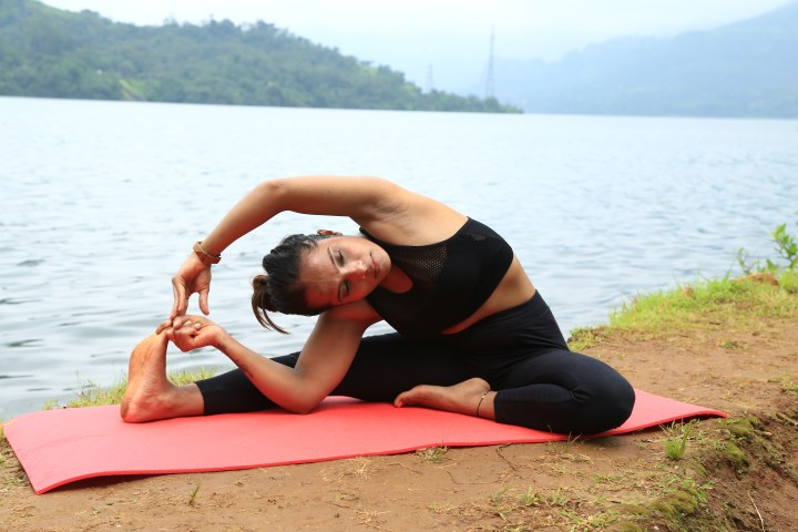 A girl doing Revolved Seated Forward Bend Pose as a part of her fitness routine