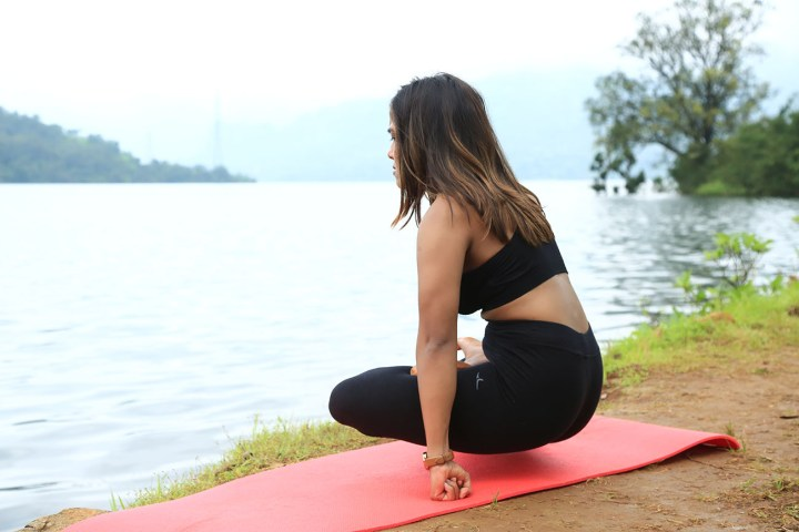 a girl performing the elevated lotus pose to strengthen arms for the elephant trunk pose in yoga