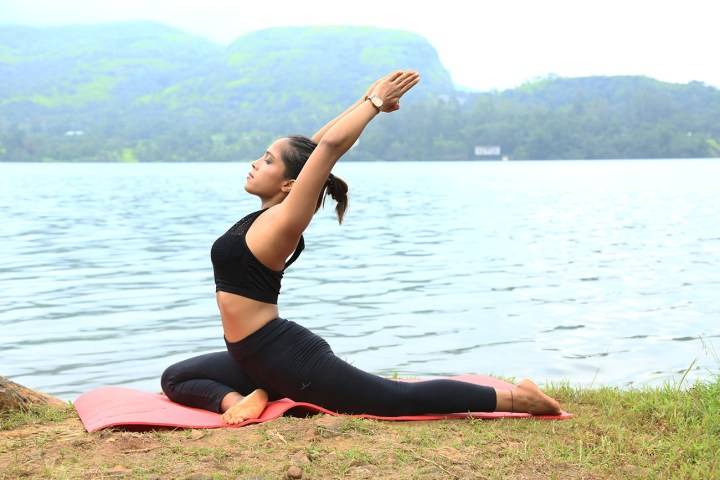 A girl doing Pigeon Pose as a part of her fitness routine