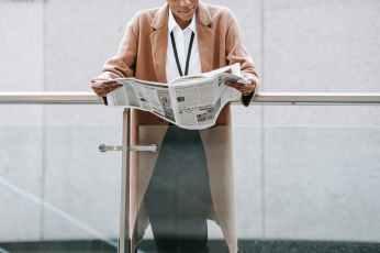 crop black businesswoman reading newspaper near modern building