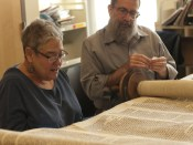 Evelyn looks on as Rabbi Druin repairs the torah.