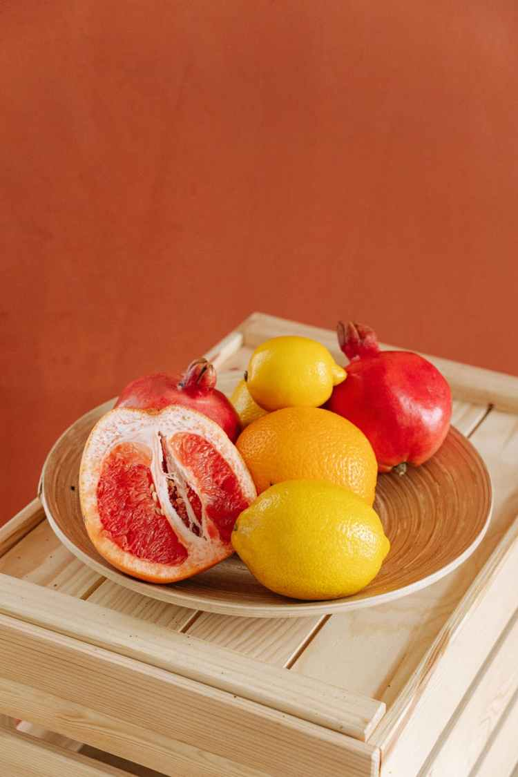 red and yellow citrus fruits on brown plate