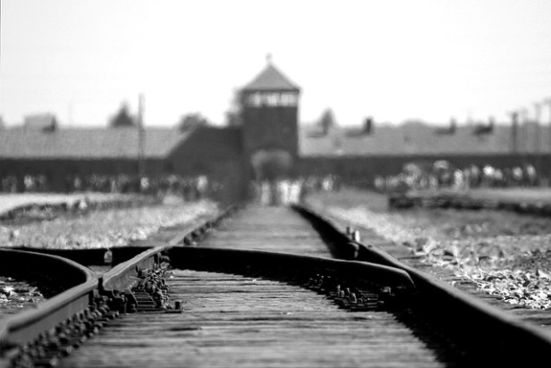 Holocaust short stories image:black and white photograph of the entrance to the Birkenau extermination camp and part of the railway line leading up to it.