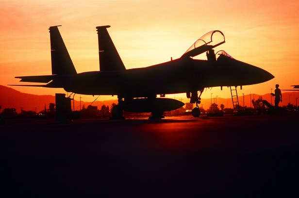 A colored photograph of F15 fighter silhouetted by rising sun - about page- political thriller author, Aaron David Yeoman
