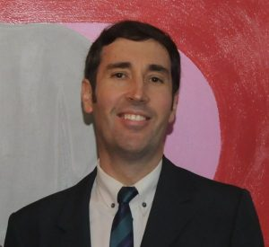 Colored photograph of head and shoulders of smiling man with dark hair, wearing dark suit, white shirt and dark tie. Background painted in 3 colors grey , pale pink and dark pink.