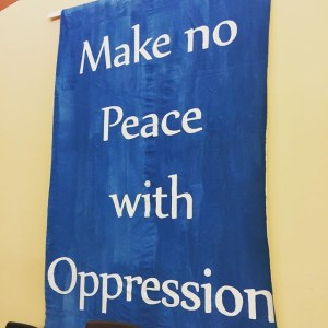 """A hand painted blue banner reads """"Make no Peace with Oppression"""""""