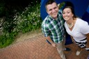 Laura & Aaron pose in front of a large blue ampersand in a brick garden courtyard