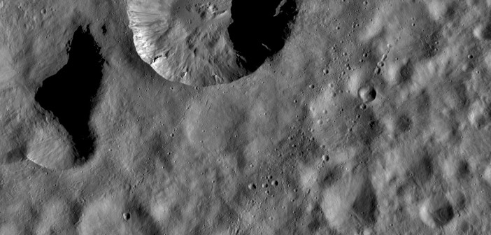 An image of the asteroid Vesta's cratered surface. The dust flung from asteroids when they are impacted can tell us about their composition. [NASA/JPL-Caltech/UCLA/MPS/DLR/IDA]
