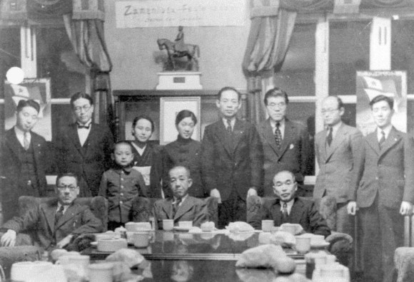 Song's grandparents (3rd and 5th from the left) and her father (the small boy in the picture) at a meeting of the Korean Esperanto club.  Posters at both ends of the frame depict the Esperanto flag.