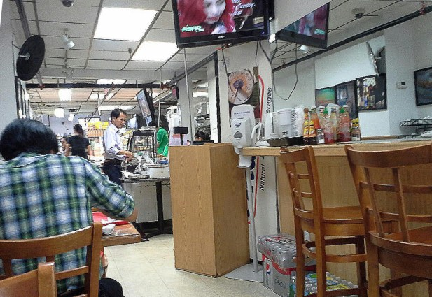 Customers in the cafe area at Phil Am Food Market can watch television shows and movies in Tagalog. Photo by Lai Wo.