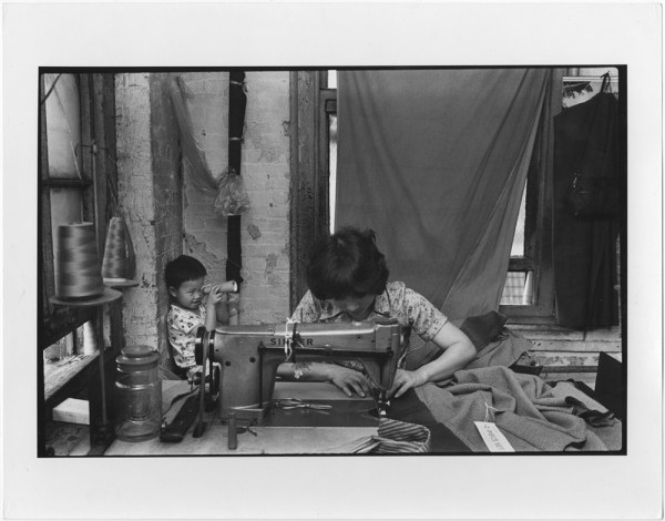 A woman sewing at a garment factory on Canal Street with a child sitting behind her. 1979-1982. Courtesy of Paul Calhoun, Museum of Chinese in America (MOCA) Collection