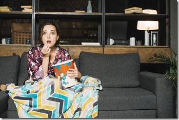 Femme assise sur son canapé devant tv