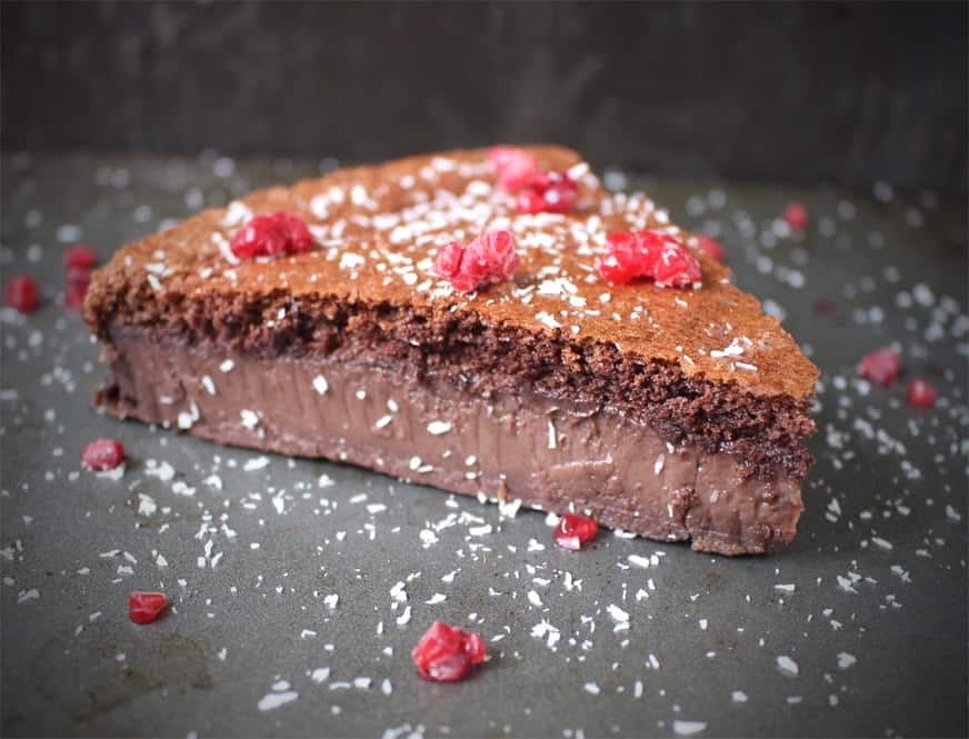 one slice of cake with raspberries and shredded coconut