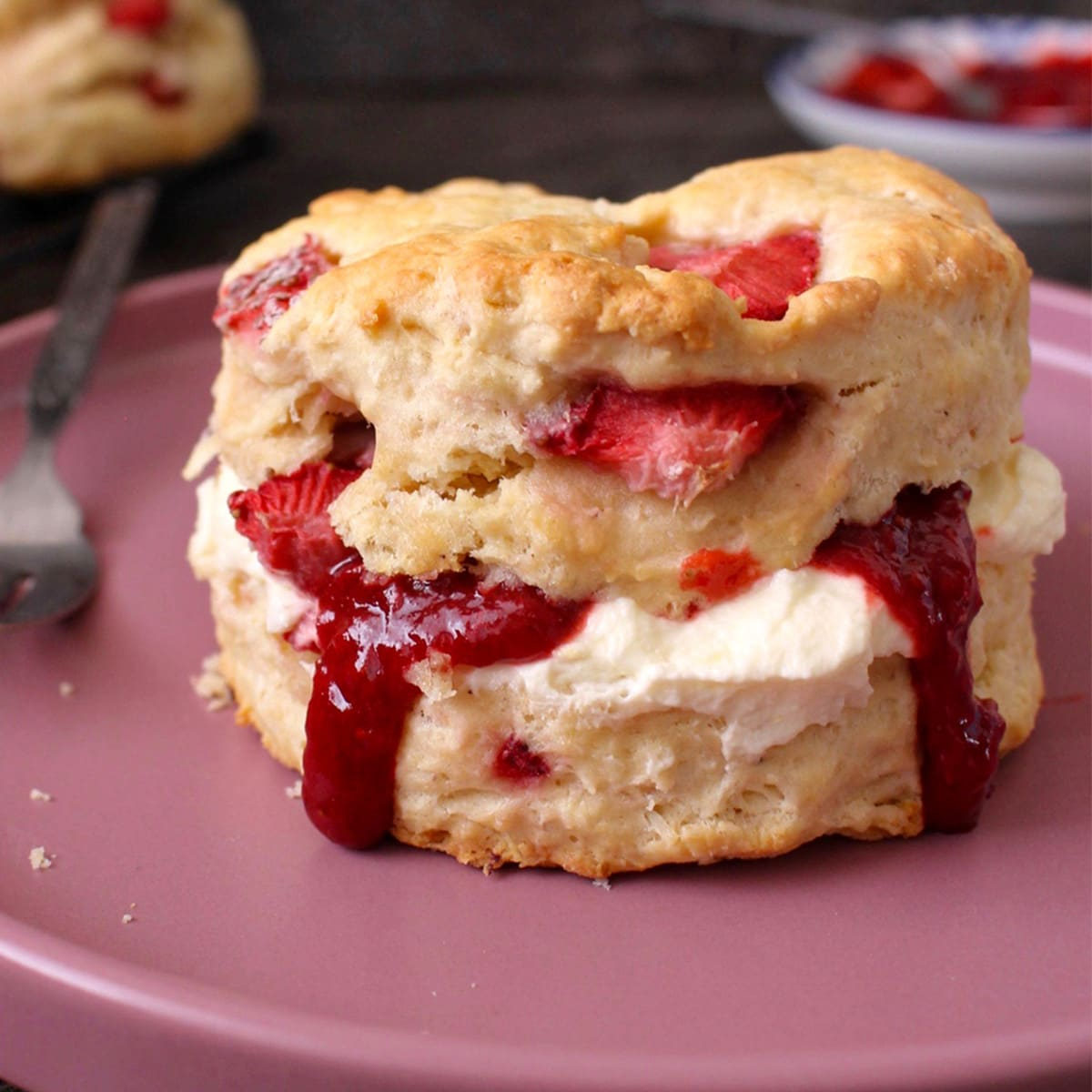 One scone filled with cream and jam over a pink plate